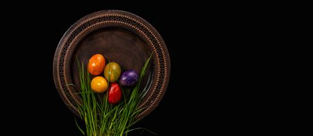 Colored easter Eggs in a plate with black background and copy space. With grass and flowers