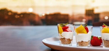 white plate with strawberries and mango. Lifestyle food served in glasses