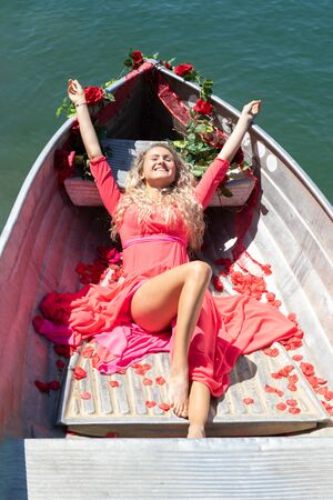 romantic scene with female model with long blond hair on a boat. Life style Shooting of a girl