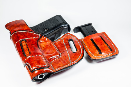 9 mm handgun in a leather holster isolated on white  photo