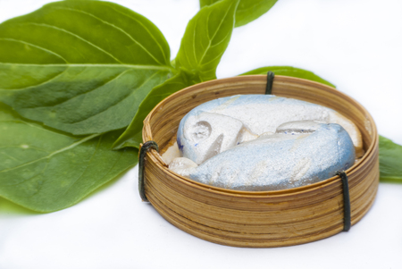 Sculpture mackerel fish in bamboo basket  on white background. photo
