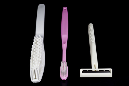 long handled: Toothbrush,comb,shaving razor on a black background