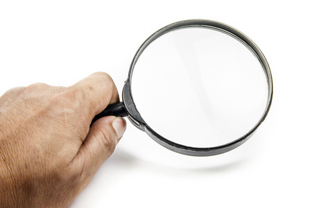 Mans hand, holding classic styled magnifying glass