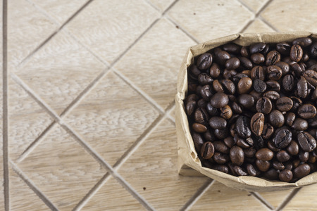 brown paper bag: Coffee beans in a brown paper bag on wooden background.