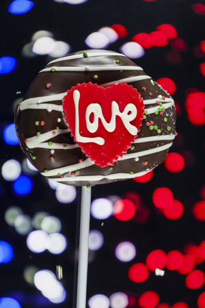 Chocolate of love in heart on bokeh background. photo