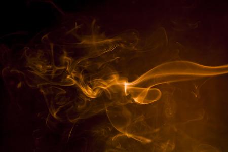 humo: Humo de oro sobre fondo negro. Foto de archivo