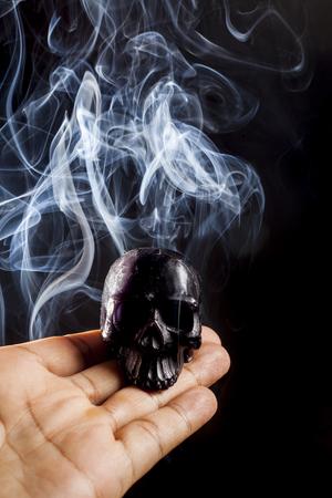 black magic: Black magic on hand with smoke on the skull.