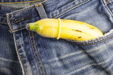 safe sex: Condom and banana ready for safe sex on jeans background.