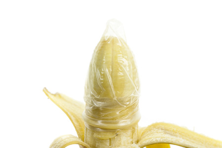 safe sex: Condom and banana ready for safe sex on white background.