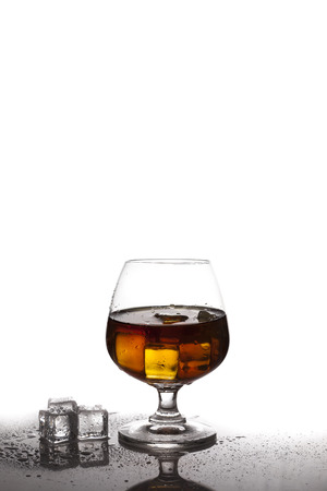 ices: whiskey in glass with ices on table white background Stock Photo