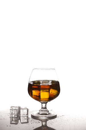 ices: whiskey in glass with ices on table, white background