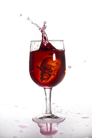 dangerous: Skull in glass of red wine. Stock Photo