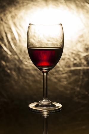 copa de vino: Vino rojo en vidrio sobre un fondo de oro. Foto de archivo