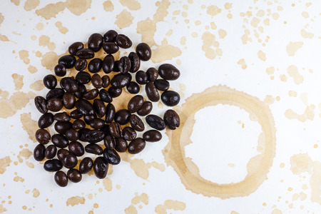 topple: Coffee beans and coffee stains on a white tablecloth. Stock Photo