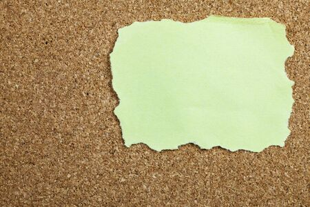 corkboard: Crumpled yellow sticky note on cork board.