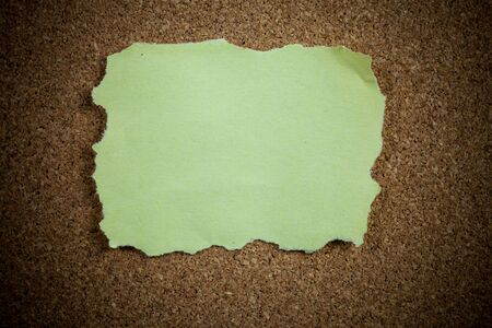 coordinated: Crumpled yellow sticky note on cork board.