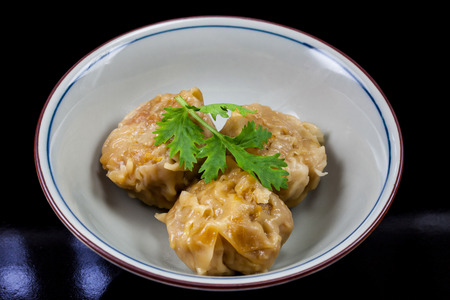cha: Chinese yum cha, pork dumpling Shumai in white bowl.