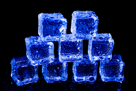 ice cubes in blue light on a black table.