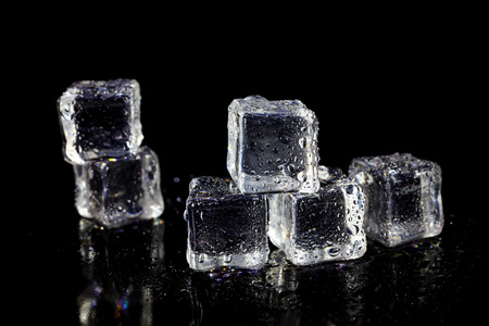 refrigerate: ice cubes reflection on black table background. Stock Photo