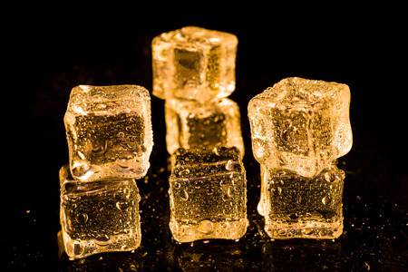 refrigerate: Ice cubes of gold color on a reflective surface.