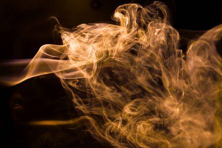 Gold smoke movement on black background.