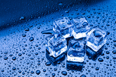 Wet ice cubes and water drop on blue background. Stock Photo