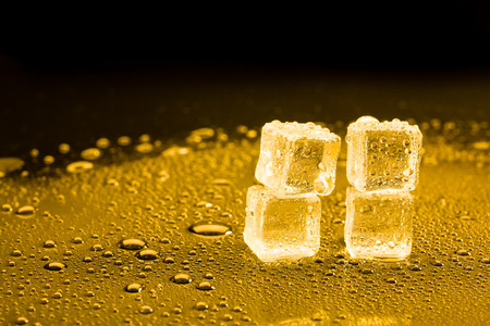 golden light: ice cubes and water drop on light golden background.