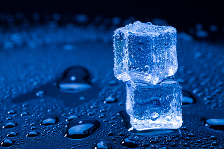 crushing: Wet ice cubes and water drop on blue background. Stock Photo