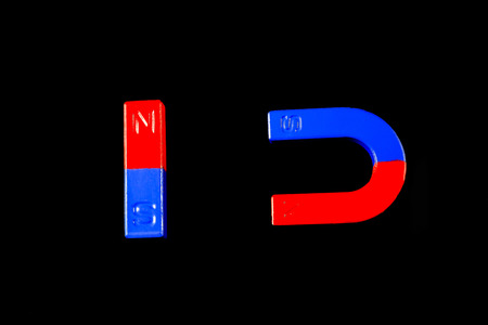 dipole: Magnetic red and blue on a black background. Stock Photo