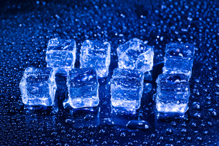 refrigerate: Ice cubes in blue light on black wet table.