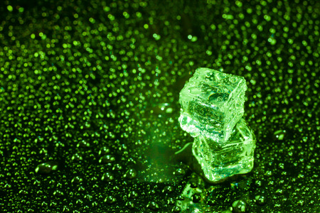 Ice cubes in green light on black wet table. Stock Photo