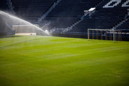 Jets de agua rociando un estadio de fútbol.