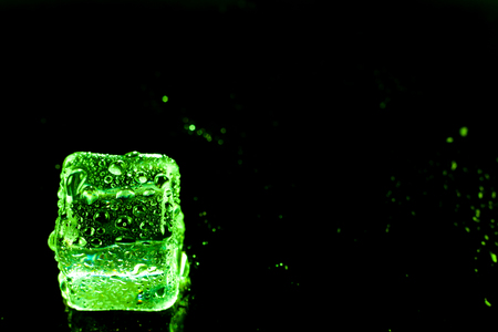 crystal background: Green ice cubes on black wet table. Stock Photo