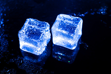 refrigerate: Blue ice cubes on black wet table. Stock Photo