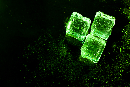 refrigerate: Green ice cubes on black wet table. Stock Photo