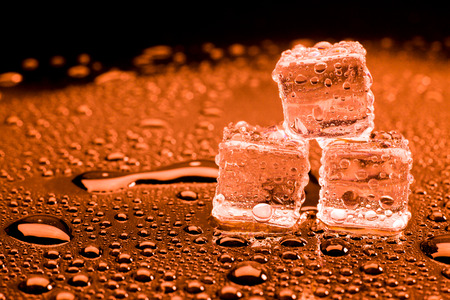 refrigerate: Water drop with ice cubes on lighting red background. Stock Photo