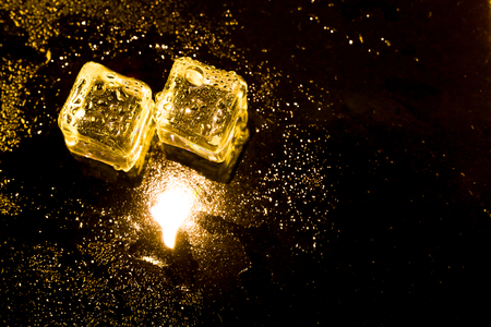 refrigerate: ice cubes and water drop on light golden background.