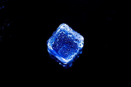 solid background: Blue ice cubes on black wet table. Stock Photo