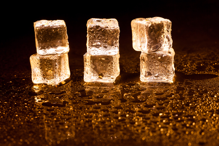 Golden ice cubes on black background.