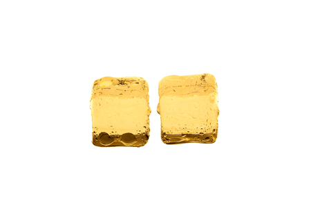 Golden ice cubes on white background. Stock Photo