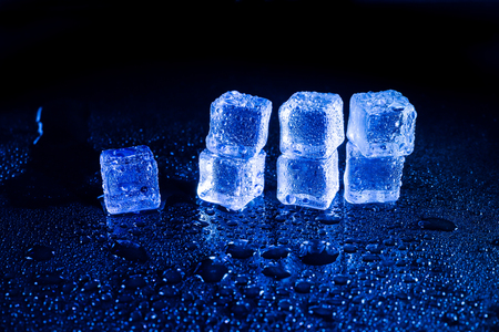Blue  ice cubes on black wet table.