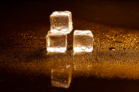 Golden ice cubes reflection on black table. Stock Photo
