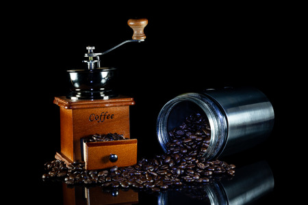 Coffee beans and vintage wooden coffee grinder on black background. Stock Photo