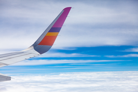 Aircraft Wing on blue sky and white clouds background.