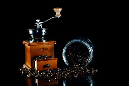 Coffee beans and vintage wooden coffee grinder on black background. Standard-Bild - 114449717