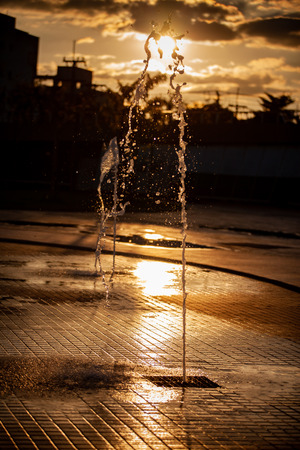 Splashes of water and bokeh of Water on a Sunset Background. Standard-Bild - 114449724