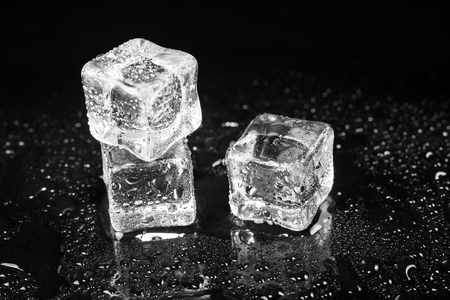 Cubitos de hielo sobre fondo negro de mesa.