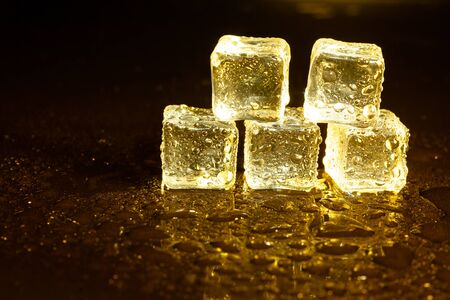 ice cubes on a reflections yellow light. Stock Photo