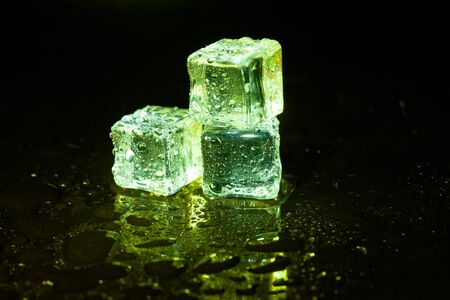 Green ice cubes on black table background. Banco de Imagens - 127921615