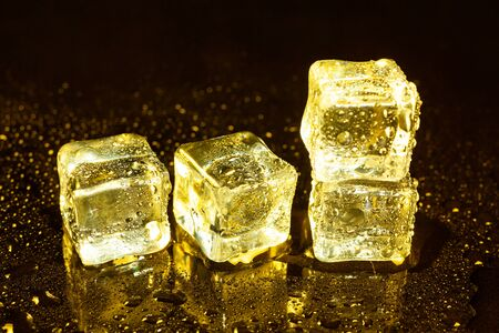ice cubes on a reflections yellow light. Banco de Imagens
